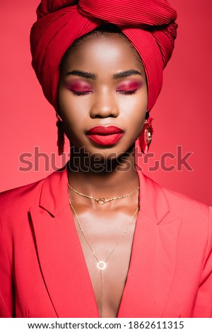 african american young woman in stylish outfit and turban with closed eyes isolated on red Royalty-Free Stock Photo #1862611315