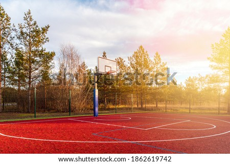 An empty basketball court found in the outdoors during autumn season