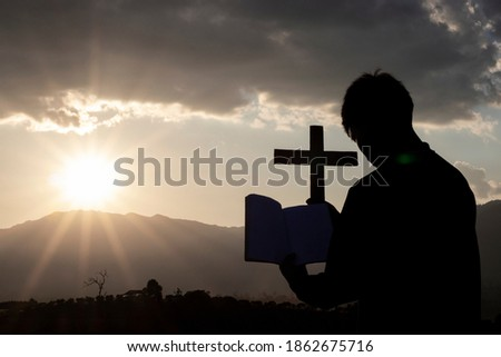 Silhouette of human kneeling down praying and holding christian cross for worshipping God at sunset background. Christian, Christianity, Religion copy space background.