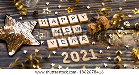 Banner.Happy New Year 2021. A symbol from the number 2021 with Golden balls, stars, sequins and a beautiful bokeh on a wooden background. The concept of the celebration.