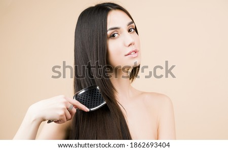 Brunette straight hair. Perfect woman with with a comb? Beautiful woman with long and shiny hair. Care. Female model after hair procedure. Natural health glance hair on beige background Royalty-Free Stock Photo #1862693404