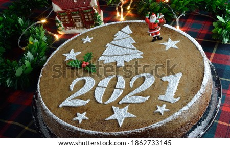 Concept with traditional Greek new years cake,vasilopita, decorative with a mistletoe and a saint claus, red tassels,artificial pine and red berries sticks around #1862733145
