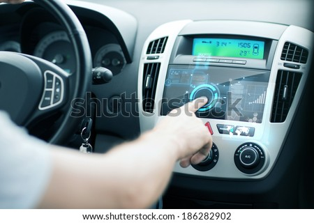 transportation and vehicle concept - man using car control panel #186282902