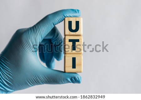 UTI (Urinary Tract Infection) - is an acronym on cubes held by a hand in a blue glove. Medical concept. Royalty-Free Stock Photo #1862832949