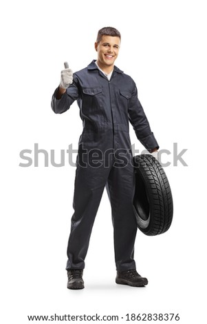 Cheerful auto mechanic worker holding a car tire and showing thumbs up isolated on white background Royalty-Free Stock Photo #1862838376