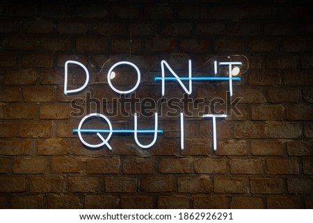 A neon sign with a message on the brick wall