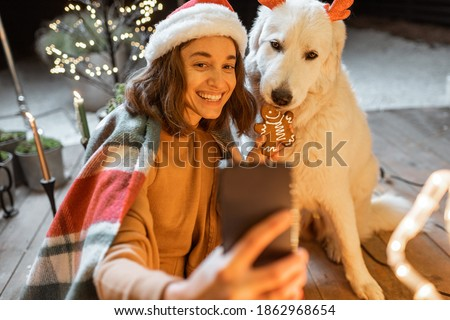 Portrait of a woman in christmas hat and plaid with her cute dog celebrating a New Year holidays at home, feeding dog with gingerbread cookies and making selfie photo