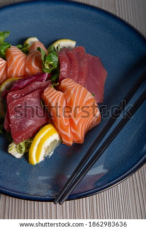 Sushi, traditional Japanese cuisine. Various delicious sashimi in the blue plate on wooden background. Vertical picture