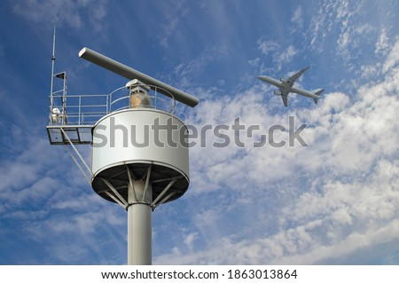 Rotating coastal radar surveillance station under the cloudy summer sky by the sea catching an airplane flying in the air space Royalty-Free Stock Photo #1863013864