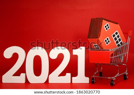 Shopping Home Property 2021 , 2021 number wood with House model on Shopping cart - Red background - home new year - Red concept of Real Estate, Property for Sale and Buy #1863020770