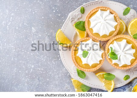 Lemon tartlets, Homemade shortbread mini tart cakes with lemon curd and whipped cream,white grey concrete background copy space