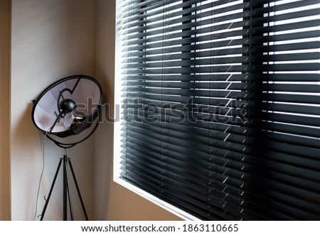 Wood blinds Coulisse black color closeup on the window in the interior. Wooden slats 50mm wide, black tapes. Venetian blinds closed in the room. There is a floor lamp near the window.  Royalty-Free Stock Photo #1863110665