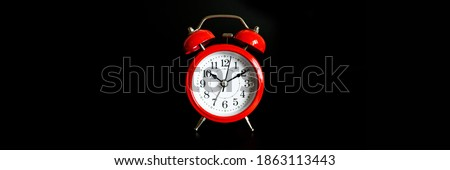 red round analog alarm clock isolated on black background. time 10:10. banner Royalty-Free Stock Photo #1863113443