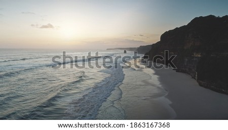 Sunrise at cliff silhouette of ocean bay coast aerial view. Summer nature scenery at sand beach with sun rise up. Nobody seascape at sunlight at sandy shore of Sumba island, Indonesia rocky shoreline Royalty-Free Stock Photo #1863167368