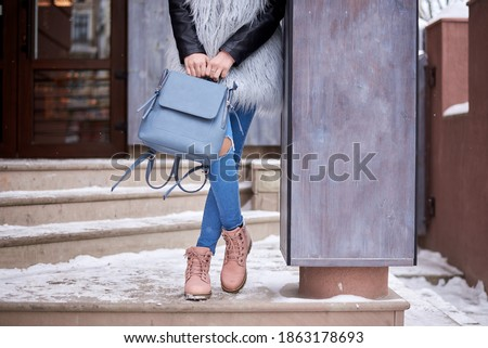 Close-up picture of female's lower body, wearing blue jeans, grey fur coat and pink boots, holding leather backpack, leaning on column. Tourist on sightseeing tour in snowy city town.