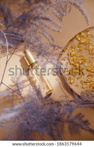 Small perfume bottle on warm pastel and golden colors table. Commercial, brand packaging mockup. Copy space. Refillable travel size. Product photography