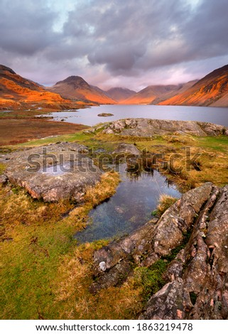Scenic view of mountains and lake at sunset with golden light and moody clouds. Wastwater, Lake District, UK. Royalty-Free Stock Photo #1863219478