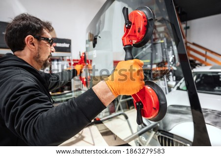 Automobile technician worker replacing windscreen or windshield of a car in auto service station garage. High quality photo Royalty-Free Stock Photo #1863279583