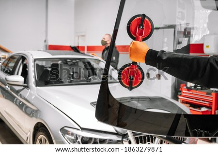 Automobile technician worker replacing windscreen or windshield of a car in auto service station garage. High quality photo Royalty-Free Stock Photo #1863279871