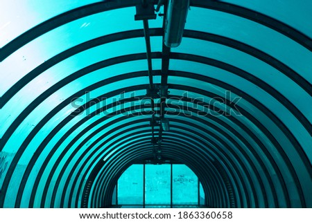 An arched tunnel across the road. Inside the overhead passage above the track. Blue light through the plastic of which the tunnel is made. A repeating element. #1863360658