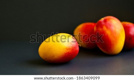 Macro photograph of a mango, with other mangoes behind and black background. Selective focus.