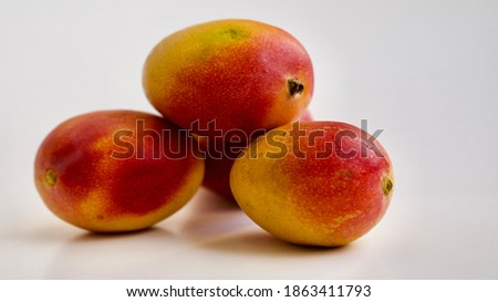 Macro photograph of a bunch of mangoes with white background. Selective focus.