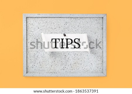 Tips word on a grey cork notice board on orange background. Top tips or quick advice concept