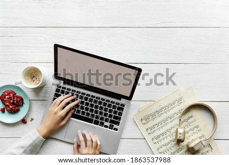 Aerial view of woman using a computer laptop on wooden table music workspace concept