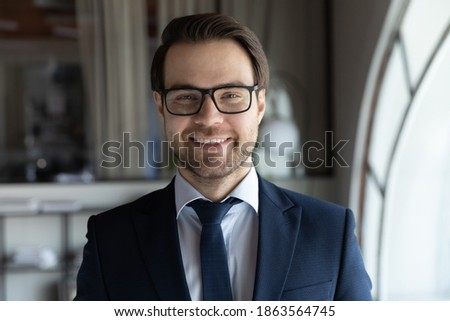 Headshot portrait of smiling motivated young businessman manager teacher in formal suit looking at camera at office area taking part in video conversation distant training webinar, profile picture