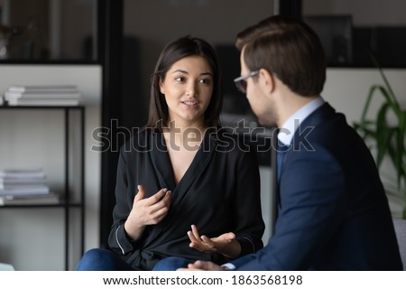 Concentrated millennial indian female candidate on vacant place answering question of male hr introducing herself on job interview, attentive man client listening to mixed race woman expert consultant Royalty-Free Stock Photo #1863568198