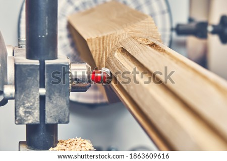 Turning wooden stair balusters. Wood stair balusters manufacturing process on a turning lathe with milling cutter. Close-up Royalty-Free Stock Photo #1863609616
