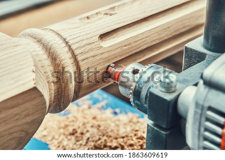 Turning wooden stair balusters. Wood stair balusters manufacturing process on a turning lathe with milling cutter. Close-up Royalty-Free Stock Photo #1863609619