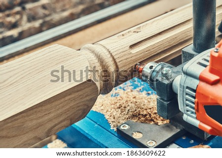 Turning wooden stair balusters. Wood stair balusters manufacturing process on a turning lathe with milling cutter. Close-up Royalty-Free Stock Photo #1863609622