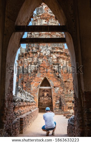 Male traveler taking pictures of a Buddha statue through wall arches, falling building, ancient ruins of Thai Buddhist temple, Wat Chaiwatthanaram, Ayutthaya historical park, Thailand, Southeast Asia