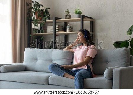 Peaceful young arabic indian mixed race ethnicity woman listening relaxing music in wireless headphones, enjoying good quality sound using online tracks playlist application on digital tablet at home. Royalty-Free Stock Photo #1863658957