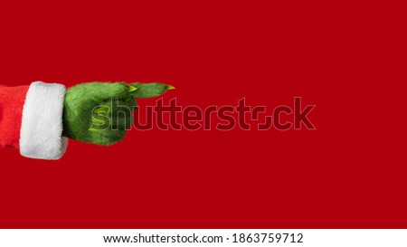 A green hairy hand in a Santa suit points to the right on a red background