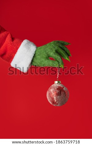 A green hairy hand in a Santa suit holds a red Christmas ball on a red background