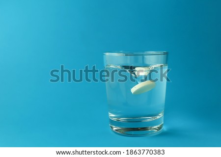 effervescent vitamin C tablet dissolves in water. a glass of water and an effervescent paracetamol tablet. the medicine tablet dissolves in a glass of water