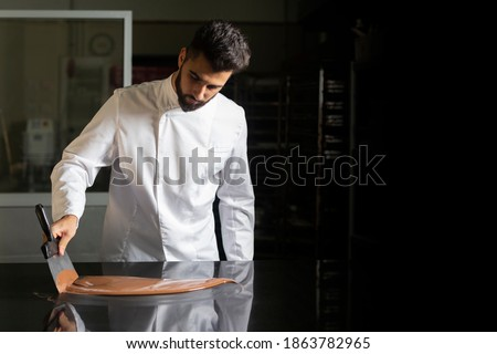 Pastry chef working on tempering chocolate on marble table Royalty-Free Stock Photo #1863782965