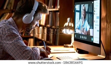 Male student wearing headphones conference video calling, watching webinar, online training class, virtual chat meeting with remote teacher or coach distance learning using computer, taking notes. Royalty-Free Stock Photo #1863816691