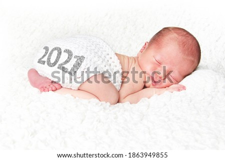 Newborn baby asleep on a white blanket with 2021on his knitted diaper cover. Happy New Year baby.   #1863949855