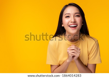 Surprised happy beauty asian woman looking camera in excitement with happy and smile face. Expressive facial expressions. Beautiful girl act like a satisfied product Isolated on yellow background Royalty-Free Stock Photo #1864014283