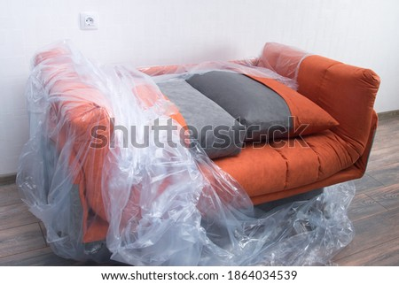 there is an orange sofa in the room, partially covered with plastic wrap to protect it from dirt and dust Royalty-Free Stock Photo #1864034539