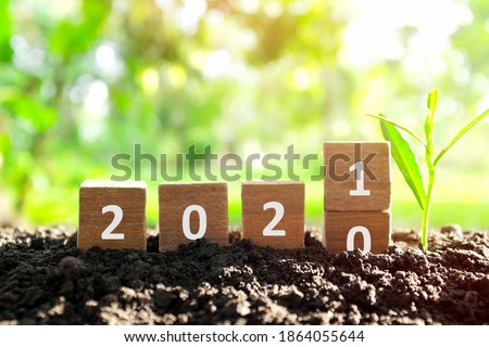 Changing year 2020 to 2021 in wooden blocks cubes with growing plant. New year, hope,  hello and goodbye concept. Royalty-Free Stock Photo #1864055644