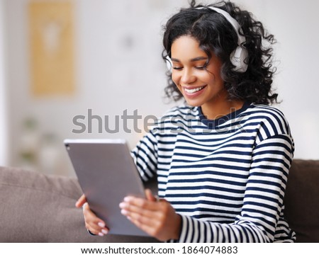 relaxed smiling young ethnic woman in casual clothes and headphones  watching movie on tablet while sitting on sofa at home