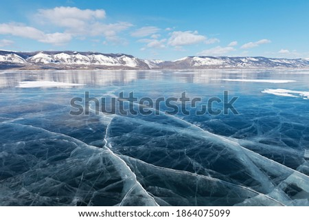 Winter landscape of frozen lake Baikal on a sunny February day. Beautiful blue smooth ice with cracks in the Small Sea Strait. Ice travel in winter holidays. Natural background (focus on ice)  Royalty-Free Stock Photo #1864075099