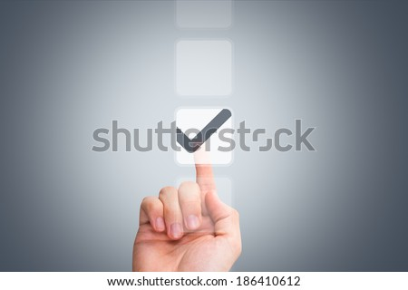 Young male hand touching, pressing modern button and ticking check box out of empty boxes on digital screen interface on virtual background. #186410612