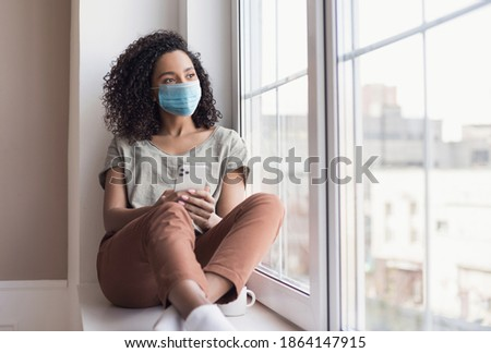 Sad woman alone during coronavirus pandemic wearing face mask indoors at home for social distancing. Mixed race girl looking at window. Anxiety, stress, lockdown, mental health crisis concept Royalty-Free Stock Photo #1864147915