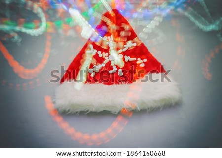 santa claus hat decorated with a snowflake of pills illuminated with colorful lights, blurred image, new year 2021