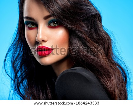 Portrait of beautiful young woman with bright blue makeup. Beautiful brunette with bright red lipstick on her lips. Pretty girl with long black hair. Closeup face of brunette woman.  Royalty-Free Stock Photo #1864243333